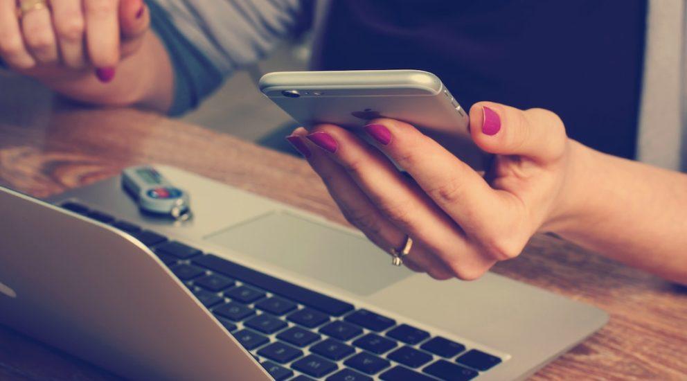 Userin sitzt vor dem Laptop und hält Smartphone