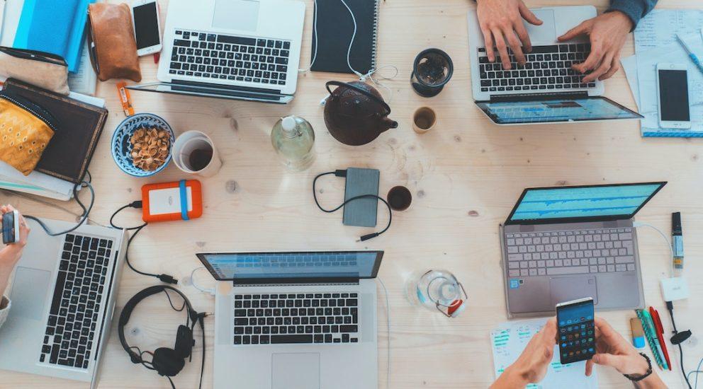 Mehrere User sitzen an einem Tisch mit den Laptops geöffnet