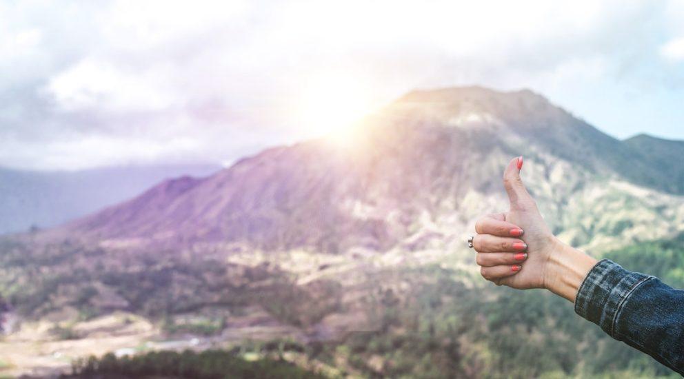 Eine Hand zeigt den Daumen nach Oben mit einem Berg im Hintergrund