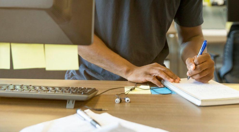 Mann schreibt auf einen Block vor einem Computer