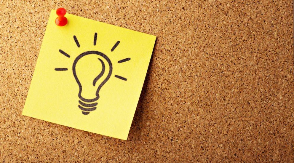 Glühbirne gezeichnet auf einem gelben Postit gepinnt an eine Korkwand