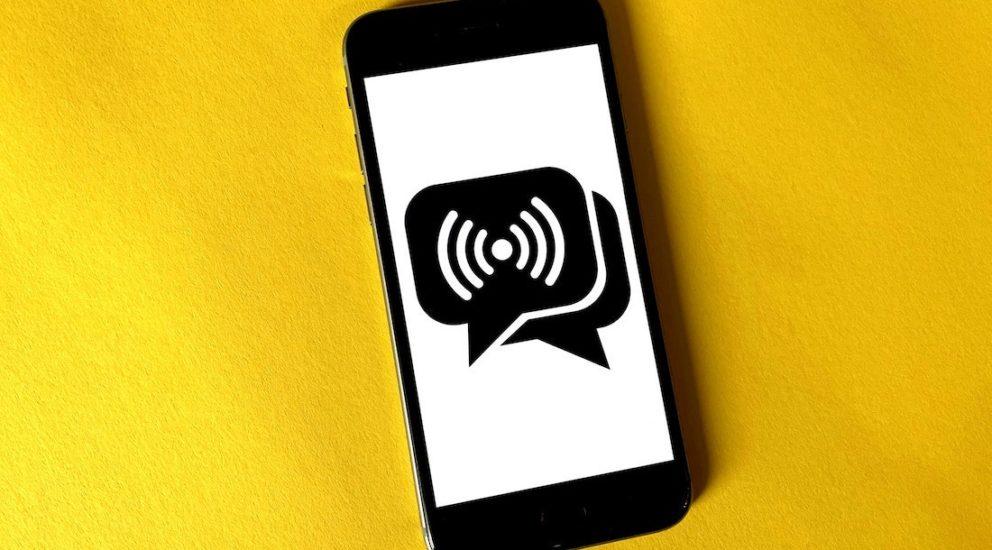 Schwarzes Smartphone auf gelbem Hintergrund mit einem Nachrichtensymbol auf dem Display