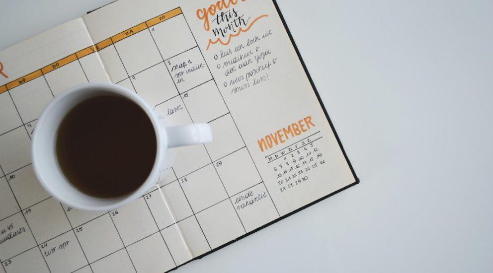 Terminplaner mit einer Tasse Kaffee darauf