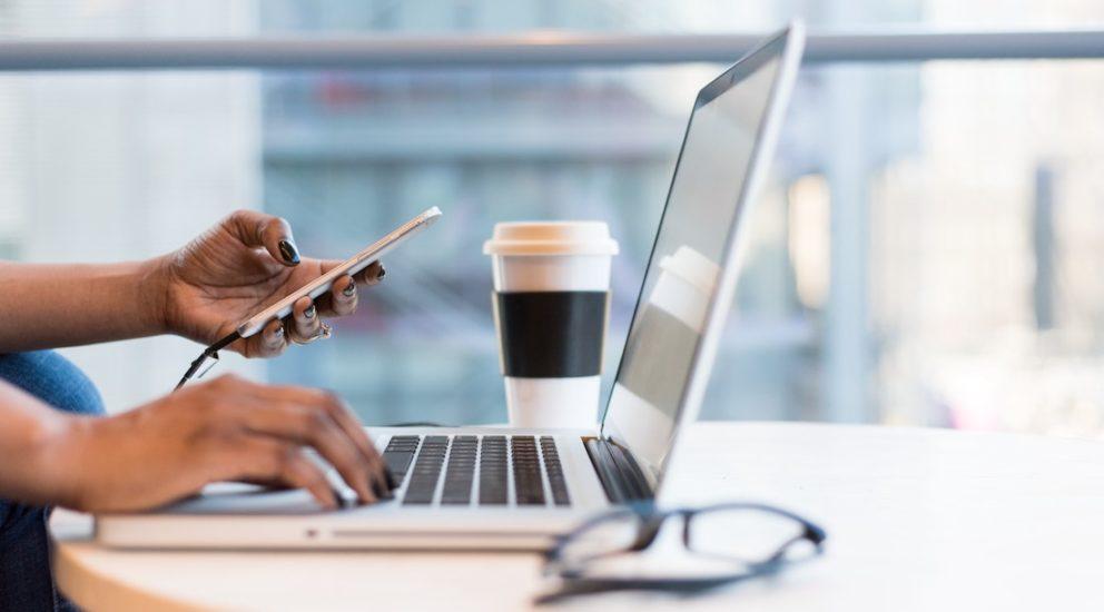 User verwendet Smartphone und Laptop