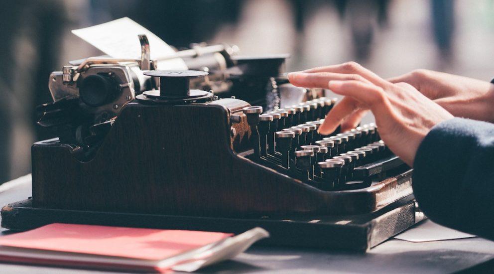 User schreibt auf einer Retro Schreibmaschine